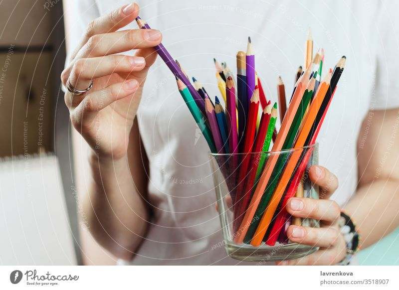 Closeup of woman picking colorful pencils from a glass creativity school drawing artist colored crayon creative designer education equipment female hand hobby