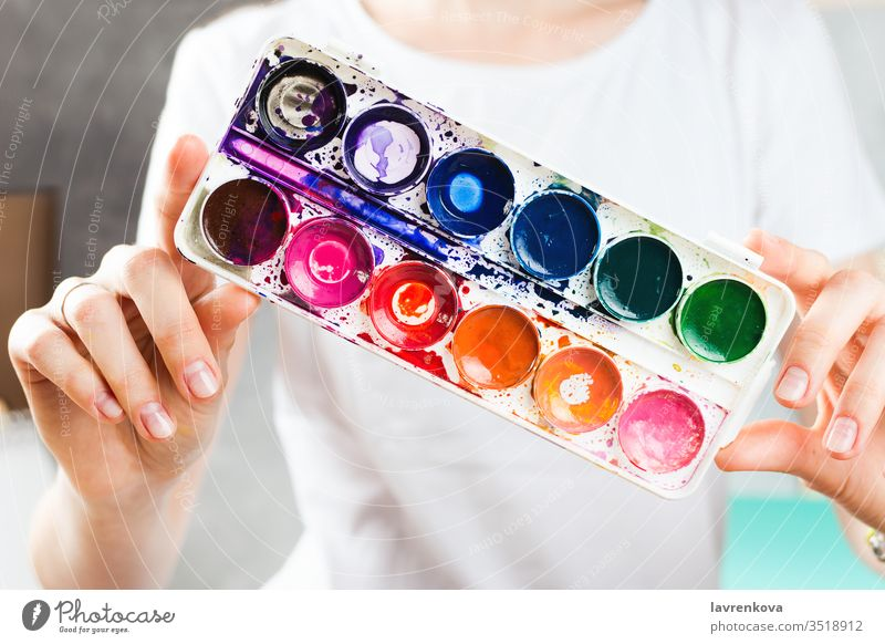 Closeup of woman holding watercolor paints in her hands craft fun creativity artist caucasian closeup colorful concept creative designer drawing education hobby