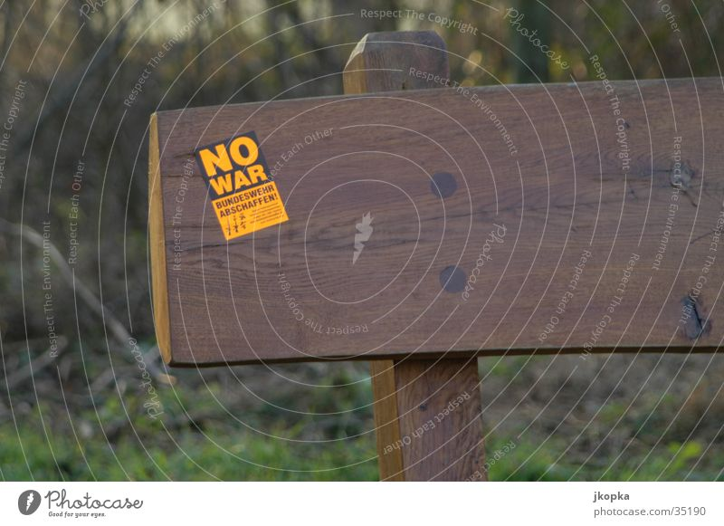 no war Freedom Culture Tree Park Forest Bench Sign Characters Signs and labeling Sit Brown Yellow Black Peace War Protest Revolt was Federal armed forces