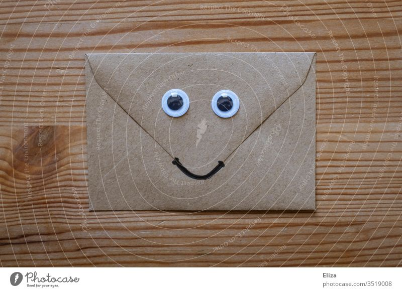 A friendly envelope with wagging eyes and a smiling face on wood Envelope (Mail) kind Face peer wobbly eyes Funny nice Letter (Mail) enjoyable communication