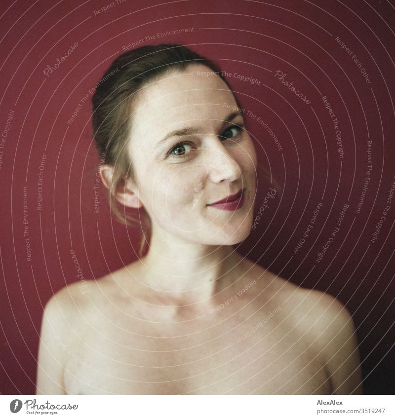 Analogue portrait of a young woman in front of a red wall Delicate Shadow Light picture-like Athletic Feminine empathy Emotions emotionally Central perspective