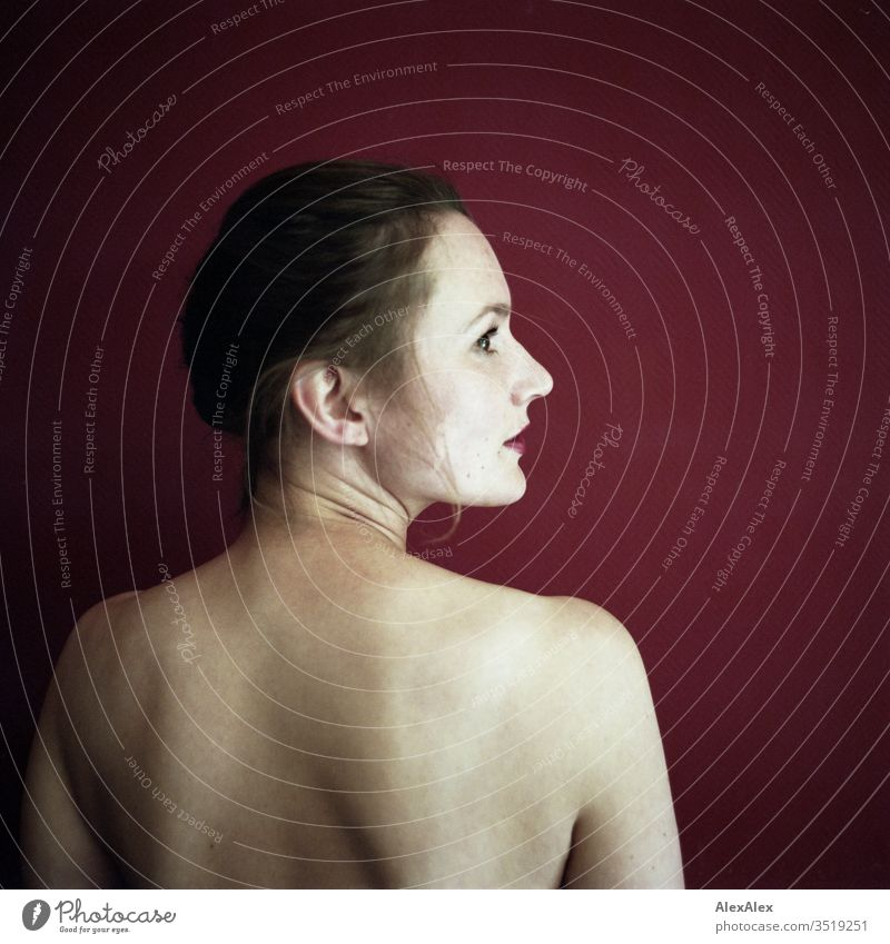 Analogue portrait in rear view of a young woman in front of a red wall Delicate Shadow Light picture-like Athletic Feminine empathy Emotions emotionally