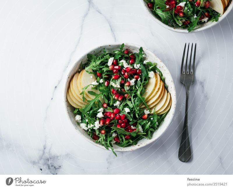 Vegan salad bowl with arugula, pear, pomegranate, cheese vegan healthy dinner food meal green vegetarian marble lifestyle homemade fresh alone plate raw