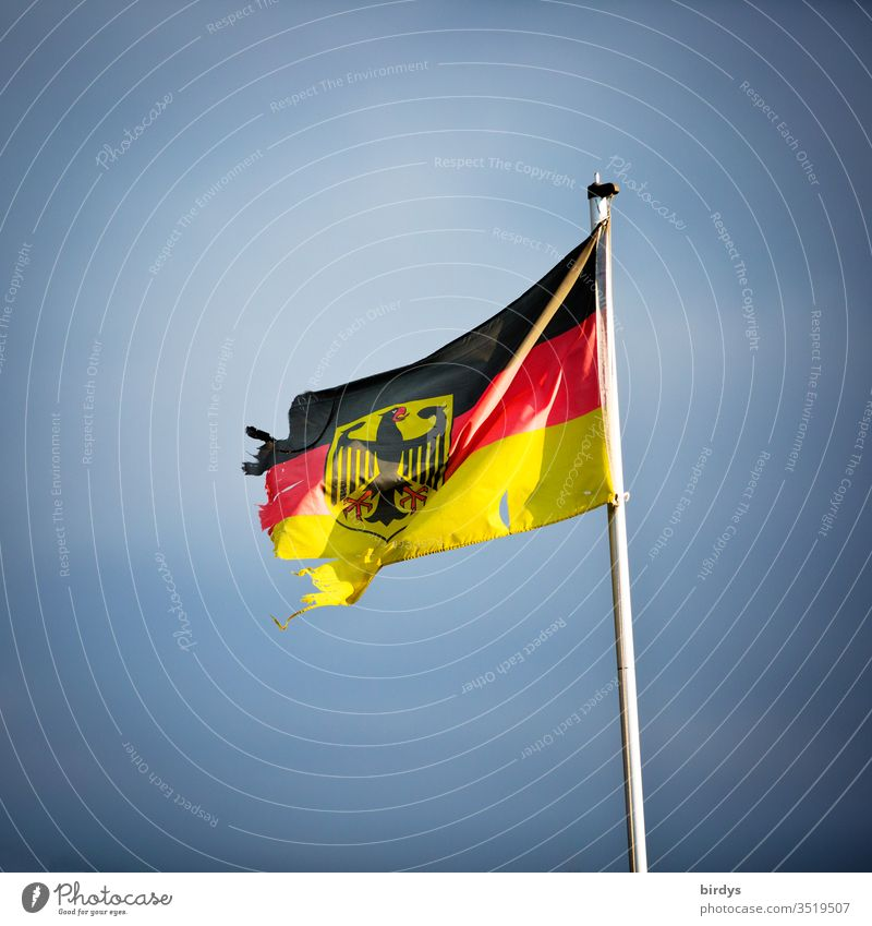 damaged German flag with federal eagle, symbolic image of instability and decomposition Germany Wind Broken torn corrupted Federal eagle German Flag Deserted