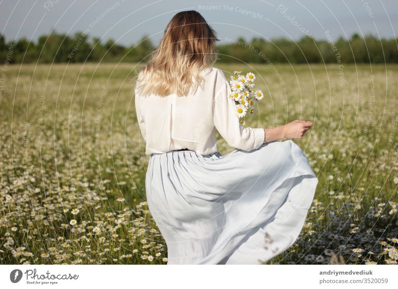 stylish young blonde woman walking in a field with daisies on a sunny summer day. flowers meadow nature people happy portrait beautiful female fun girl smile