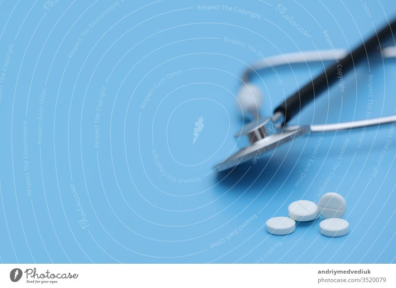 Pills spilling out of pill bottle syringe thermometer and stethoscope on blue background. medicine concept. selective focus medical treatment health white