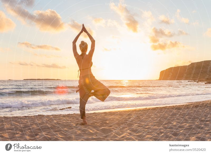 Woman practicing yoga on sea beach at sunset. peace woman girl body relax health exercise ocean sunrise spirituality zen lifestyle young sky nature outdoor