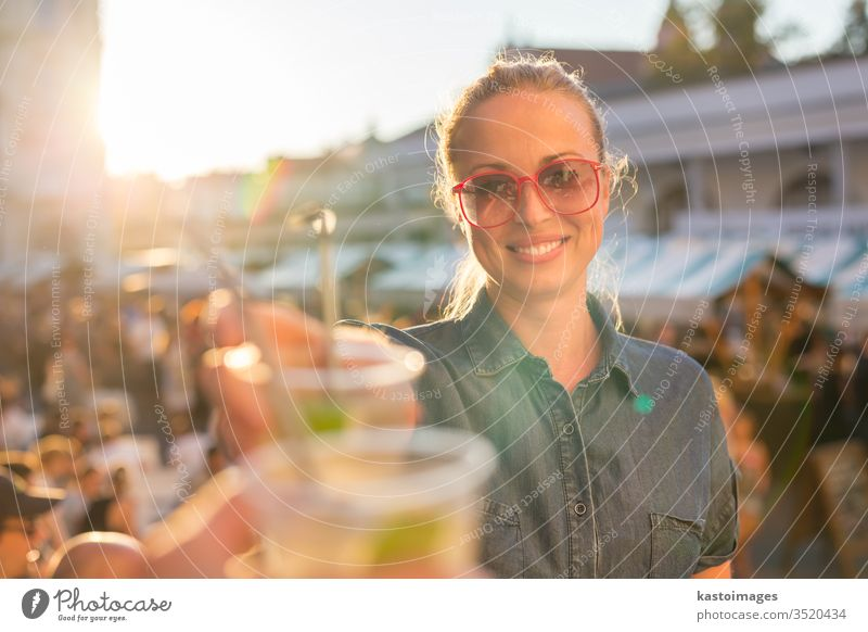 Beautiful young girl toasting on outdoor urban event. festival drink woman people music alcohol fun happiness outdoors youth city smiling celebration cheers