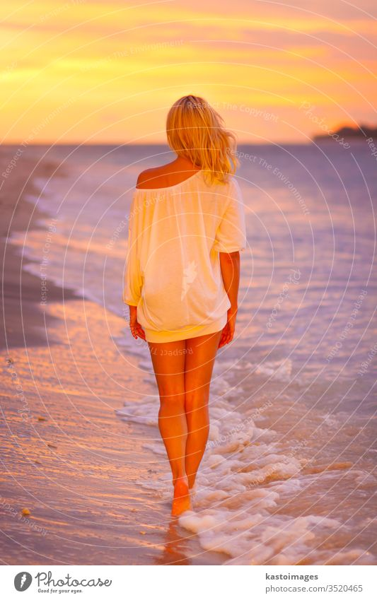 Lady on sandy tropical beach at sunset. woman ocean summer coast joy sea nature lifestyle body young white sexy silhouette person girl lady casual dress