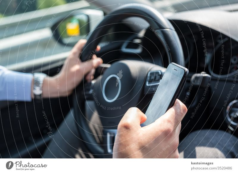 Businessman texting on his mobile phone while driving. car driver technology business person automobile using businessman dangerous traffic transportation cell