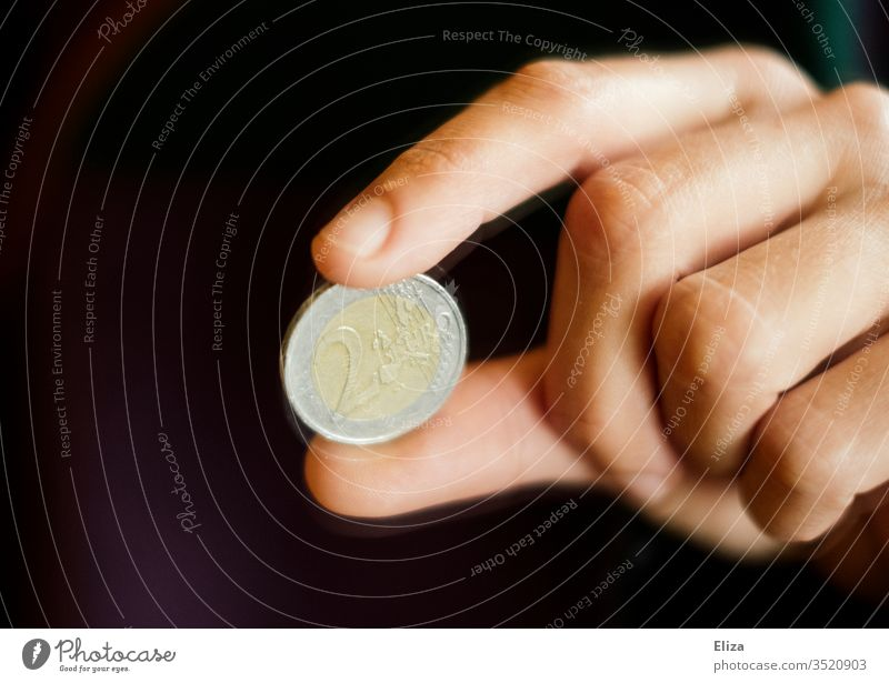 One hand holds a two euro coin between two fingers Euro euromint Coin Loose change Money finance gratuity Paying Black conceit Save Give Financial Industry