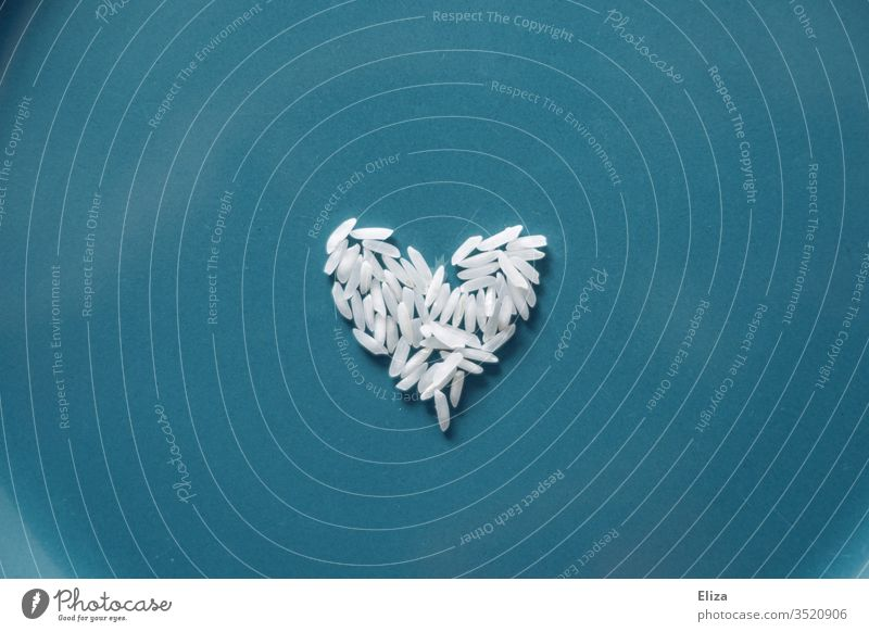 A white heart of rice grains on a blue background Rice Grains of rice Heart symbol Food food Nutrition Carbohydrates Interior shot Eating hunger world hunger