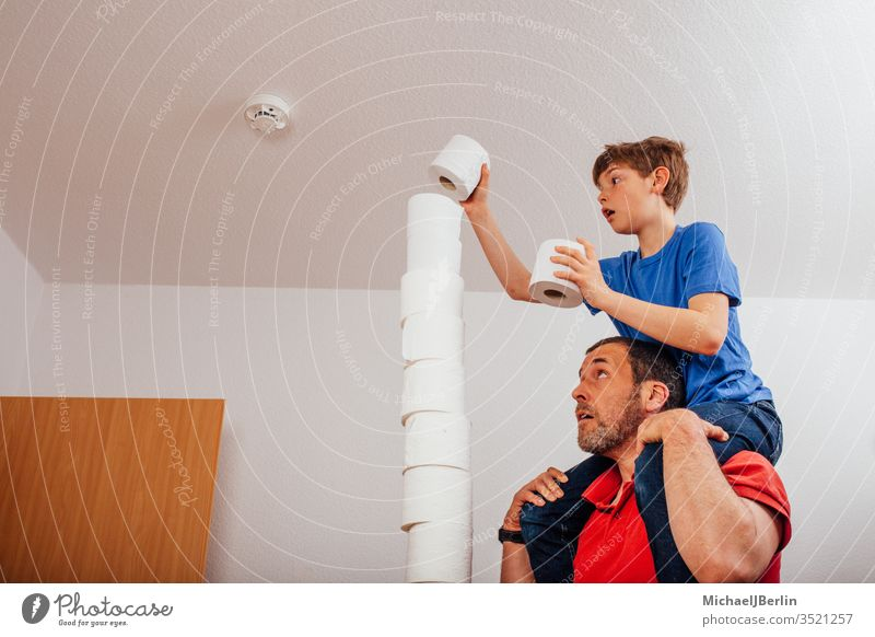 Father and son balancing stacks of toilet paper left Stack Toilet paper Balance Boredom Boy (child) challenge Child Corona covid-19 Epidemic Family game Tall