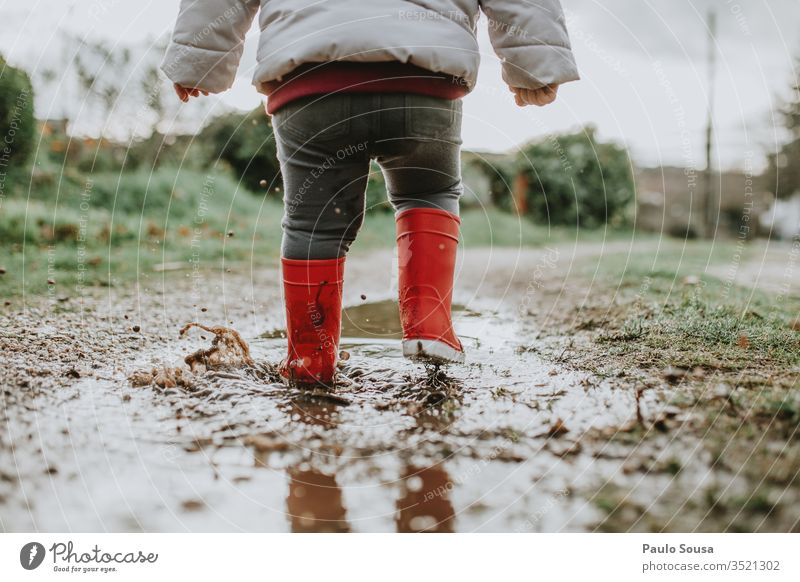 Low Section Of Baby Girl Walking On Puddle During Rainy Season Child Water Reflection Exterior shot Red Rubber boots childhood Happiness Wet Colour photo