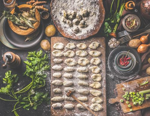 Homemade gnocchi making preparation. Potatoes dough on dark rustic kitchen table with cutting board and healthy ingredients. Tasty home cuisine. Top view. Still life