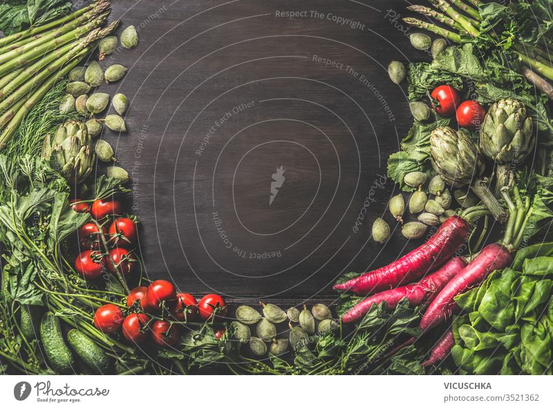 Food background with group of various fresh organic vegetables from garden on dark rustic wooden background. Top view. Healthy clean vegetarian ingredients: Tomato, lettuce, root vegetables,artichokes
