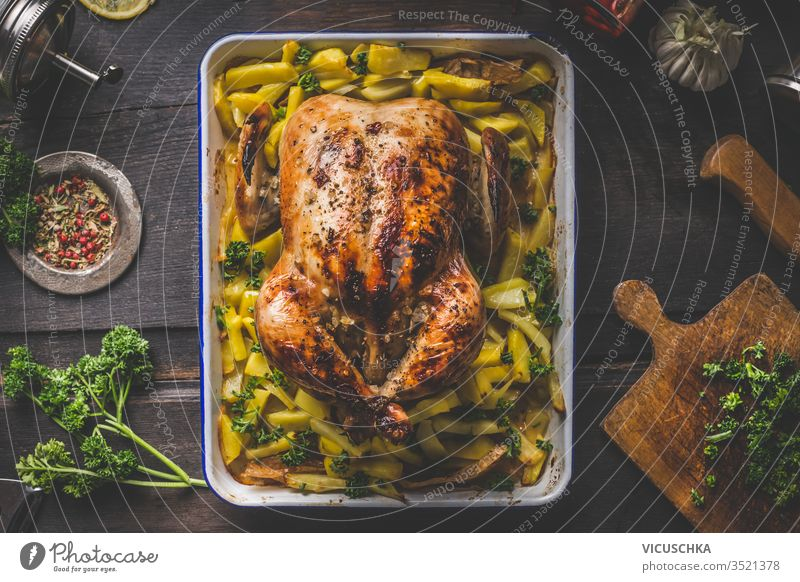 Delicious roasted whole chicken or   turkey with potatoes on dark rustic wooden kitchen table with herbs and spices. Top view. Home cooking delicious top view