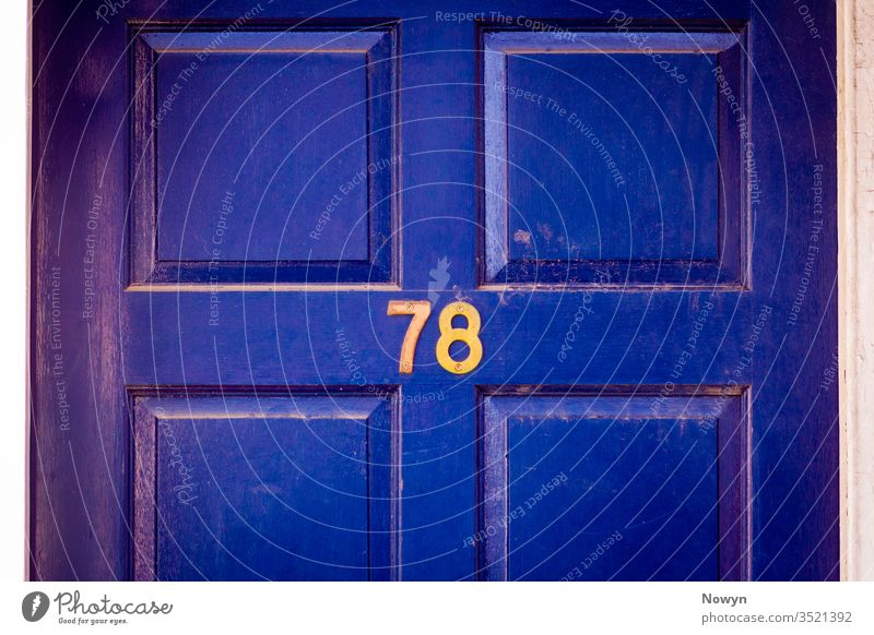 House number 78 on a dark blue weathered and worn wooden front door 78 number address britain classic classy close up closeup decoration design detail digit