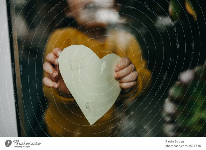Close-Up Of Hand Holding Heart Shape through window through glass holding Heart-shaped Child at home stay at home Quarantine Window prevention pandemic