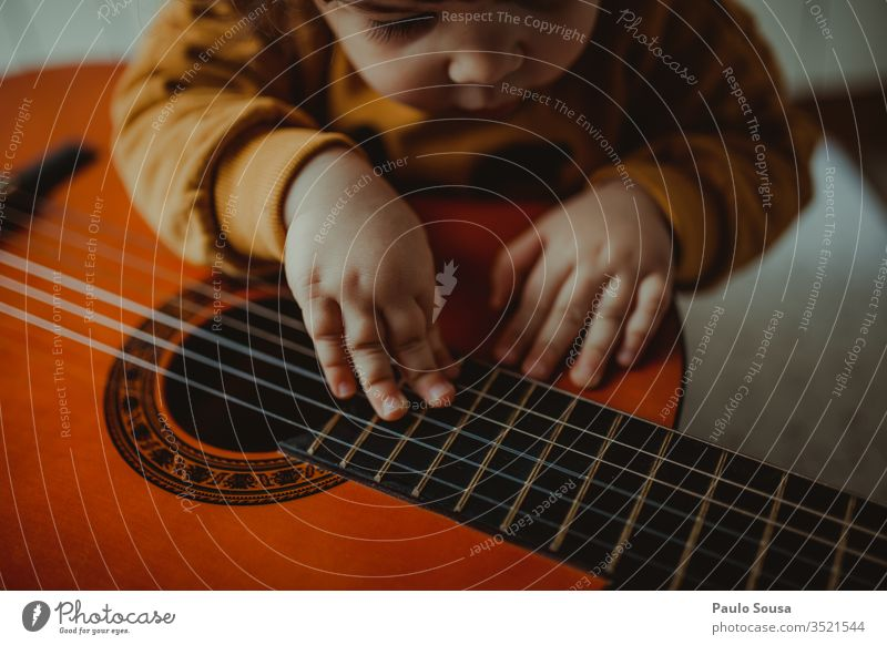 Child playing guitar Playing Happiness Caucasian indoor Curiosity Innocent Girl Home Looking cosy Joy Lifestyle Cute Infancy Happy learn Horizontal Beautiful