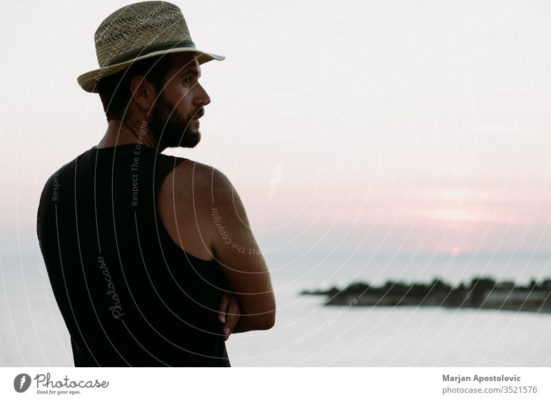 Young man enjoying sunset by the sea adult adventure alone beach coast dawn dusk enjoyment evening freedom guy handsome hat holiday horizon landscape leisure