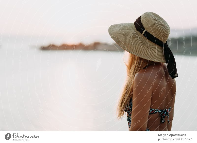 Young woman enjoying sunset by the sea adventure beautiful beauty carefree cliff coast coastal coastline evening female freedom girl hat holiday horizon