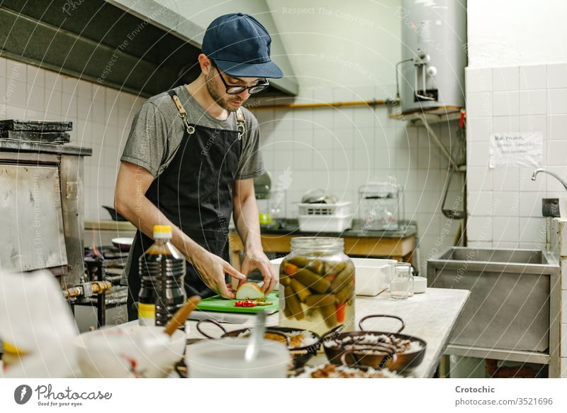 Man with glasses and a cap cooking in a restaurant kitchen with pots of food, oil and pans commercial containers elements professional stainless appliances