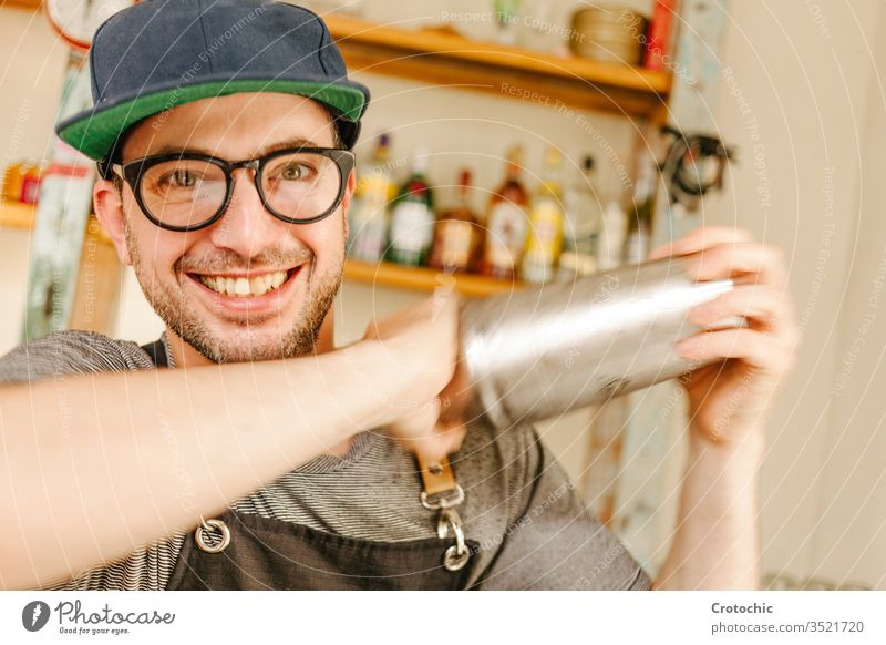 Waiter wearing an apron, glasses and a cap smiling while shaking a cocktail alcohol club fingers hold job party professional service shake bar liquor making