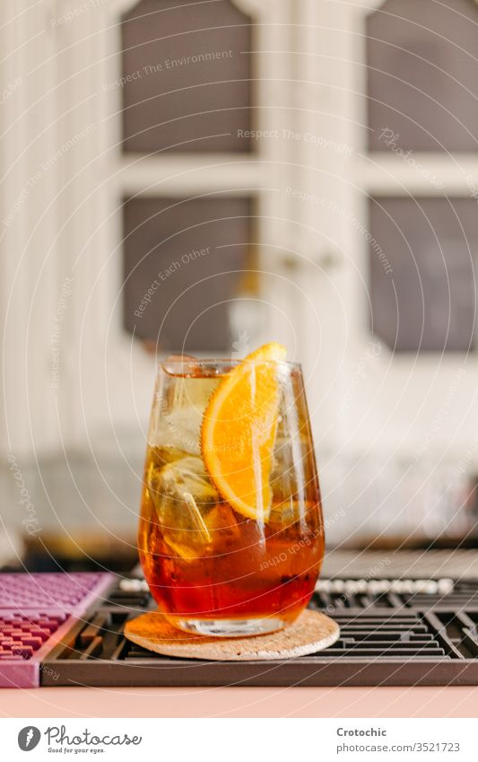 Vertical photo of a crystal glass with an iced cocktail with a piece of orange to decorate in a bar vertical drink alcohol cool freshness dark beverage garnish