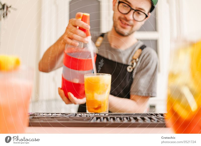 Waiter with apron, glasses and cap throwing soda into a glass with a cocktail at a bar splash mix bottle dispensed pouring ice waiter hotel fresh alcohol