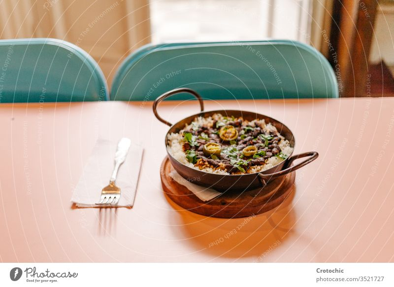 Pan with rice and beans decorated with chopped green chilies and served on a wooden table fork napkin ready hot decoration pepper design pan black exotic