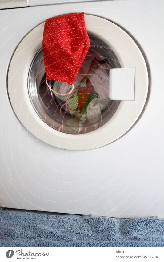 Red self-sewn protective mask made of fabric with dots, hangs before washing, disinfection on the door of the washing machine in the bathroom. Sterile face mask to protect against corona, viruses, flu, diseases and against smog, air pollution.