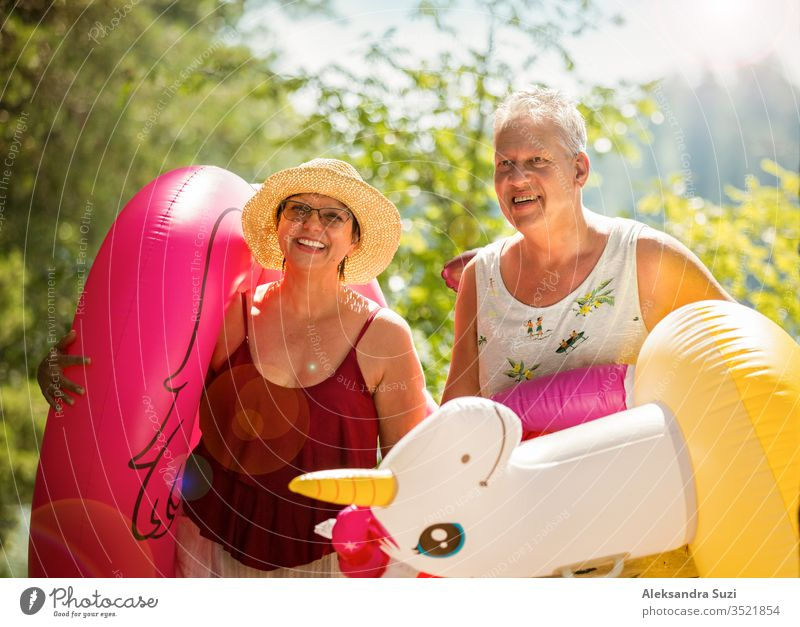Elderly couple walking a forest path along the seashore holding giant inflatable flamingo and unicorn. Funny active pensioners enjoying summer vacation on the beach in Northern Europe