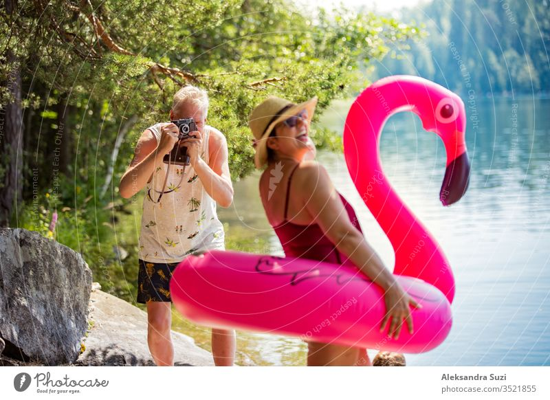 Elderly couple taking photos on vintage camera in forest along the seashore holding giant inflatable flamingo. Funny active pensioners enjoying summer vacation on the beach