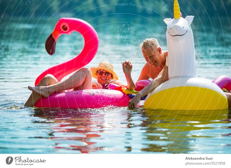 Elderly couple having fun on inflatable flamingo and unicorn. Funny active pensioners happy together enjoying summer vacation on the beach in Europe, laughing, playing the fool, splashing water.
