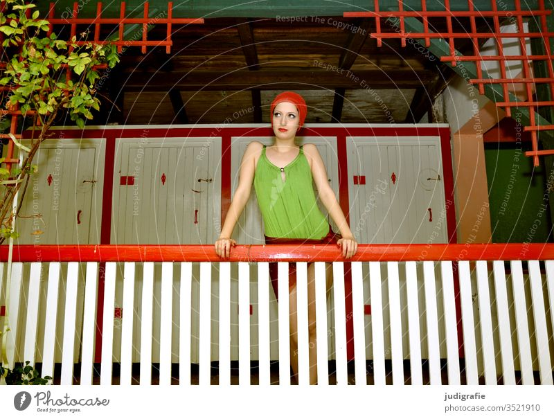 The girl with the beautiful red swim cap and green swimsuit is leaning on the railing of the ladies' changing room. A summer love. Woman Swimwear bathing cap