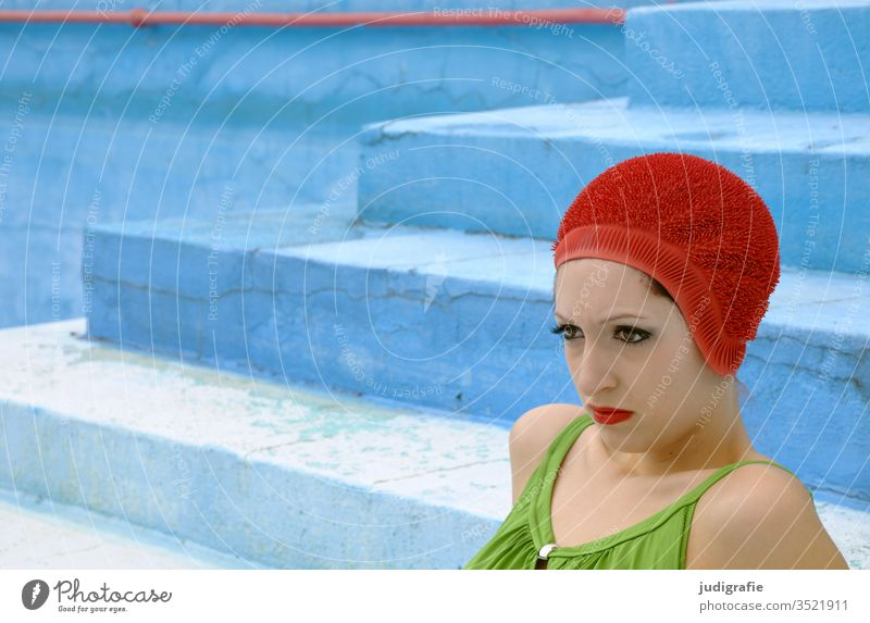 The girl with the beautiful red bathing cap and green swimsuit is sitting on the stairs of the empty non-swimmer's pool. A summer love. Woman Swimwear