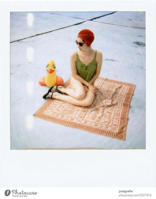 The girl with the beautiful red bathing cap and green swimsuit is sitting on a blanket with her rubber duck. A summer love. Woman Swimwear Bathing cap Swimsuit