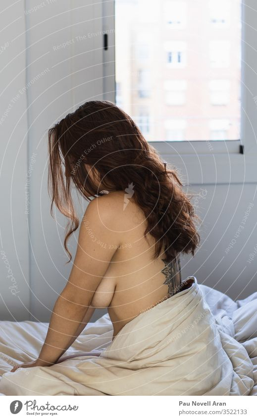 Sexy tattooed woman with beautiful long hair is sitting on bed sex naked alone girl sad home indoors lazy orgasm sexy undressed apartment bedroom blanket white