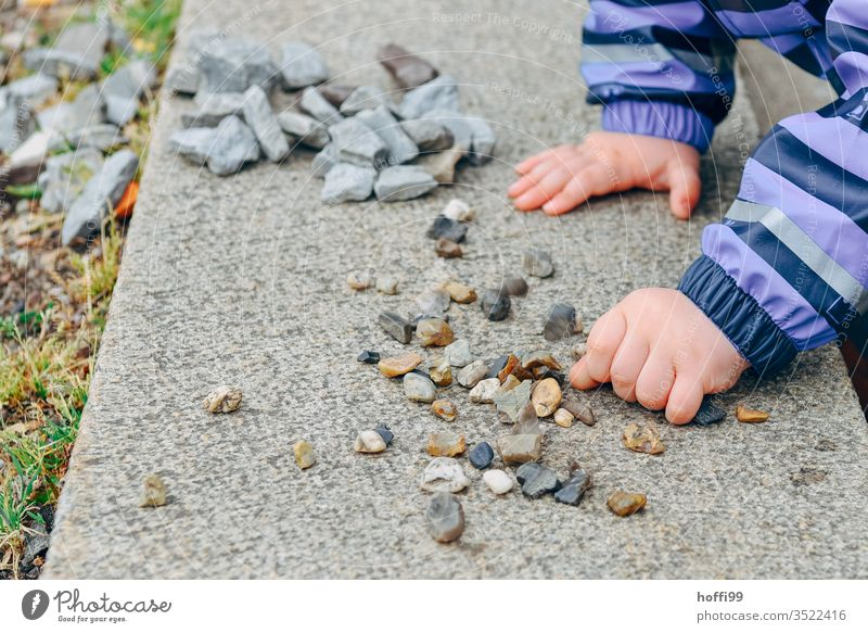 Children's hands sort small stones on a wall children's hands Children`s hand Playing Arrange by hand Infancy Toddler Colour photo Fingers 1 - 3 years Detail