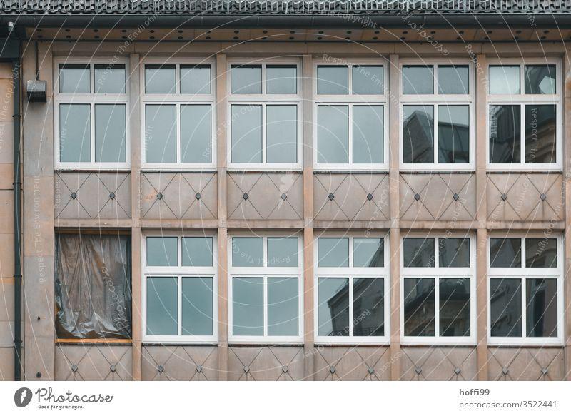 The broken window in the facade was closed with boards and tarpaulin Window Broken barricade barricaded Facade Decline repair Redevelop Old