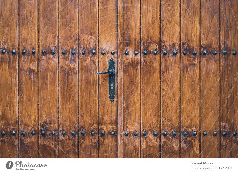 Traditional wooden door decorated with iron studs abstract background texture textural cracked peeled outdoor outdoors exterior color detail artificial urban
