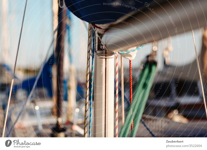 Mast and boom of a sailboat with details Pole tree Shrouds To fall husks Tree vang Mast groove Loose fitting Harbour Sailing Summer Sailing ship Sailboat Rope