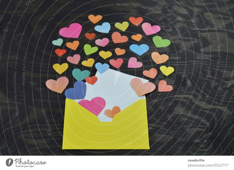 yellow envelope opened with a blank white card for self labelling, many colourful hearts cut out of paper which come out of it as a nice greeting from a distance with social distance e.g. for Mother's Day or birthday on black wood