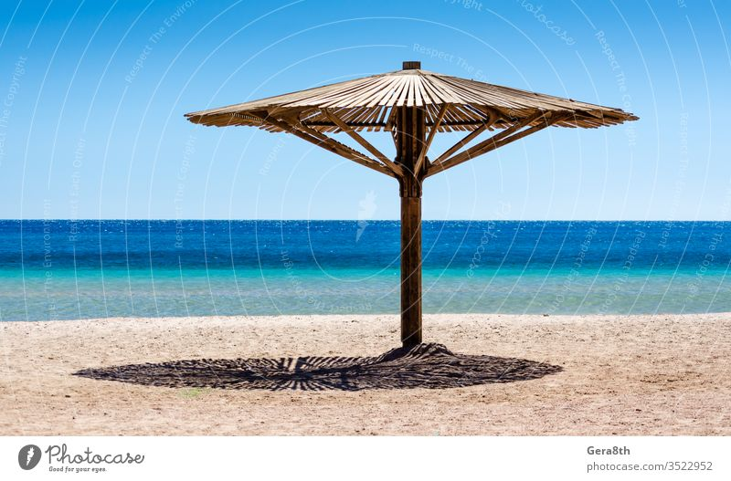 one wooden beach umbrella on the sand on the beach against the blue water of the Red Sea in Egypt Dahab South Sinai background beach background day empty