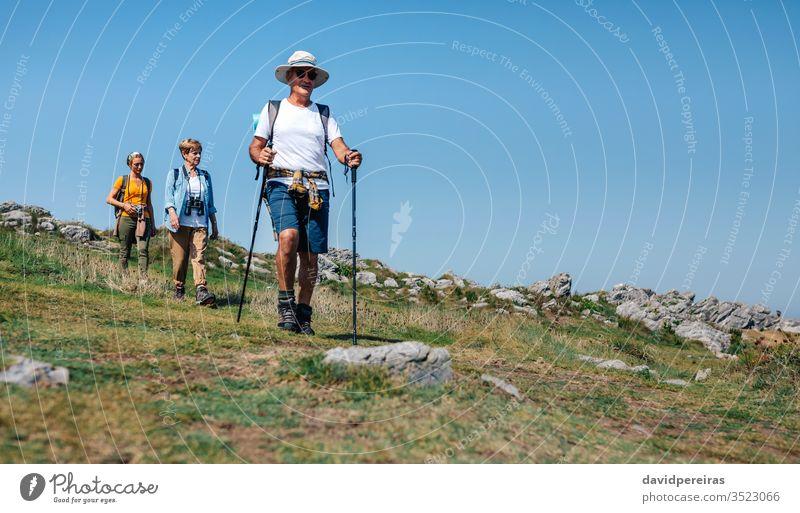 Three people practicing trekking outdoors hikers local tourism family countryside walking trekking sticks senior nature nordic walking summer landscape