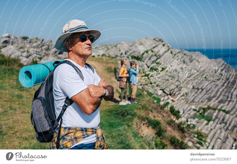 Senior man trekking looking at the landscape hikers senior retired nature hat sunglasses countryside summer mountain recreation people hiking field spring
