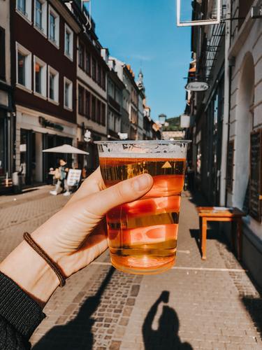 Full beer glass in the main street in Heidelberg Beer Mug Street Main street Town Downtown Beer glass Tourism Old town Baden-Wuerttemberg Europe Germany by hand