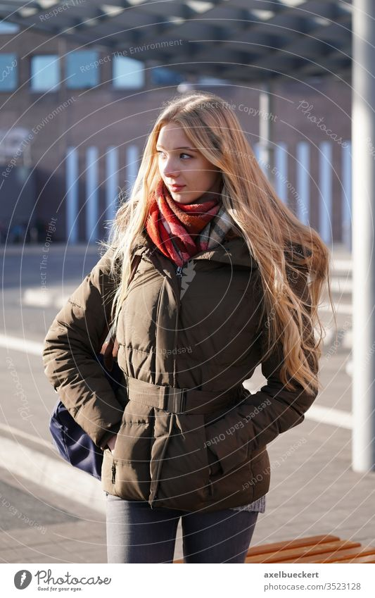 candid street style image of young woman waiting at bus station girl stop teenager real people portrait city urban lifestyle winter outside blond blonde long