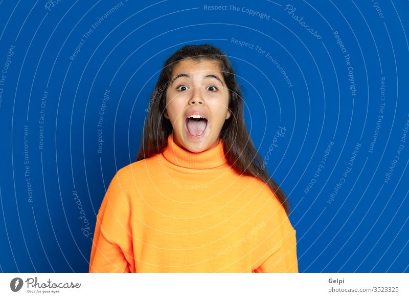Preteen girl with yellow jersey preteen blue surprised exciting crazy scary emotion amazing shout female people person pretty attractive background teenager